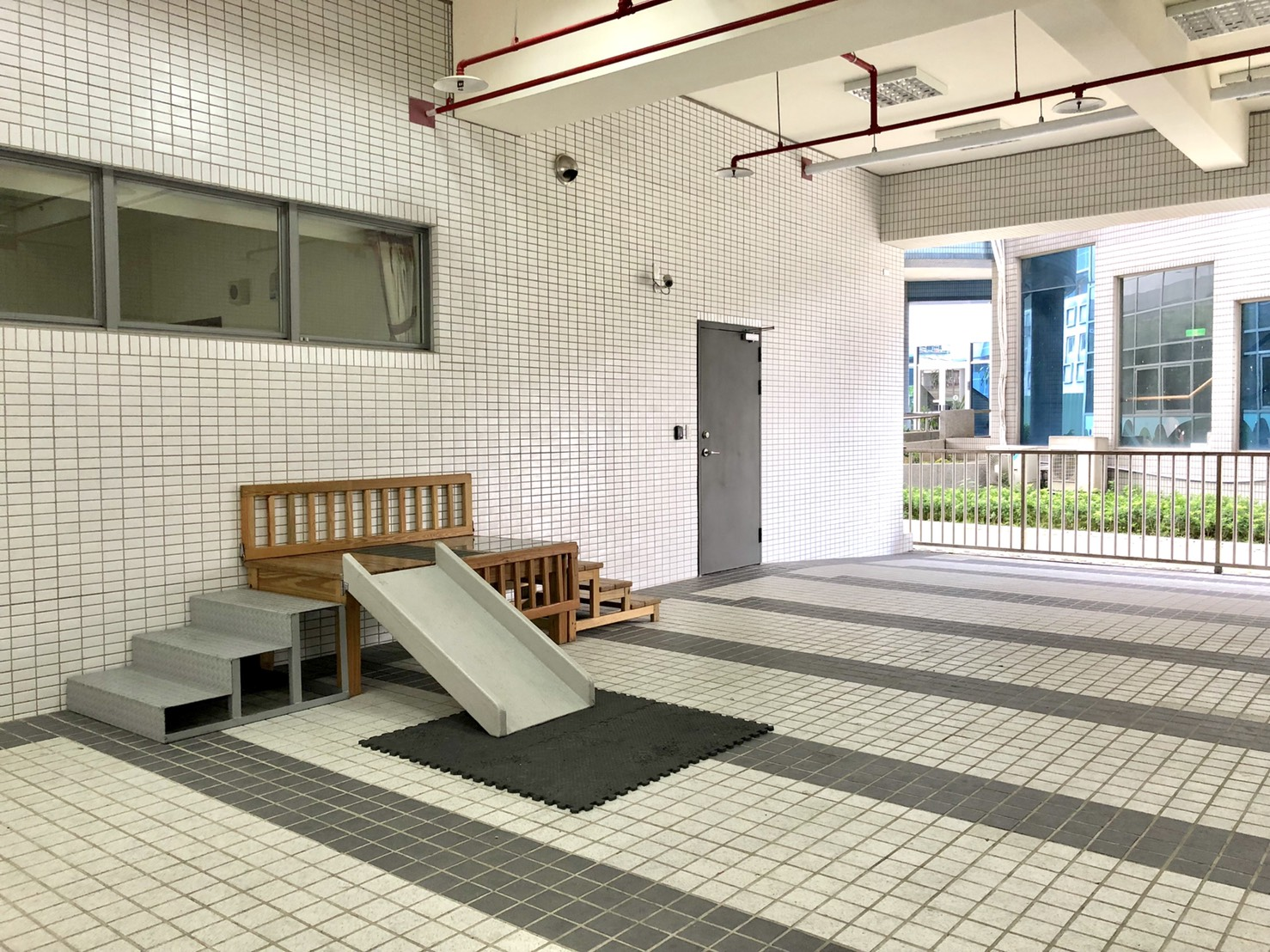 室內遊戲室,遊戲室的設施使用多種異材質製作,有模擬水溝蓋、木頭、塑膠等不同材質的地面樓梯斜坡。
